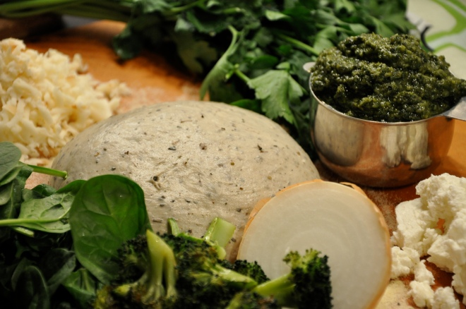 Pizza: Dough, smoked mozzarella, goat cheese, broccoli, pesto, spinach